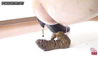 Брюнетка сидит на корточках и какает перед камерой
