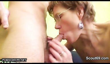 Мама в очках облизывает головку члена молодого любовника перед минетом и сексом на диване