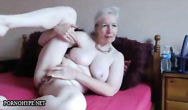 Бабушка с седыми волосами мастурбирует пилотку пальцами и секс игрушкой в спальне на кровати перед веб камерой