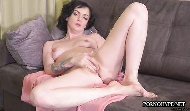 Зрелая матюра с татуировками на руках лежит на диване и мастурбирует